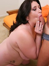 Mature big brunette licking a huge cock while titty fucking